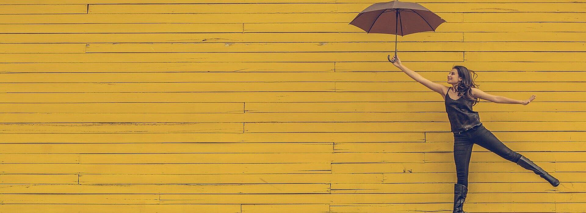 mulher segurando um guarda-chuva e pulando em um fundo de parede amarela