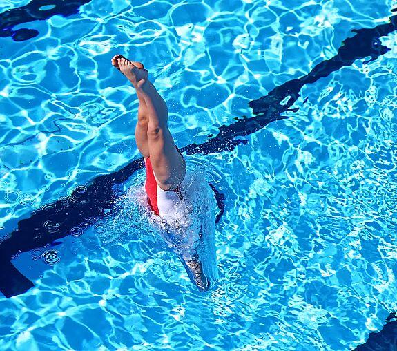 Atleta treinando nado artístico na piscina