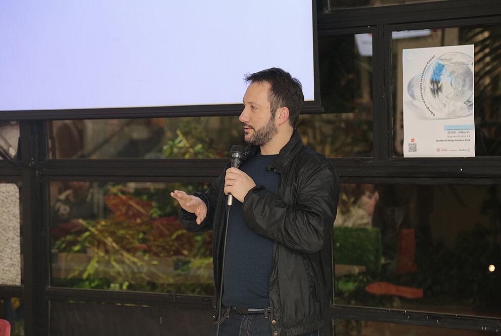Homem em pé fala ao microfone