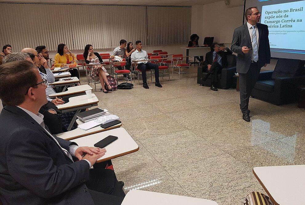 Sala cheia com dois palestrantes em apresentação, telão ao fundo