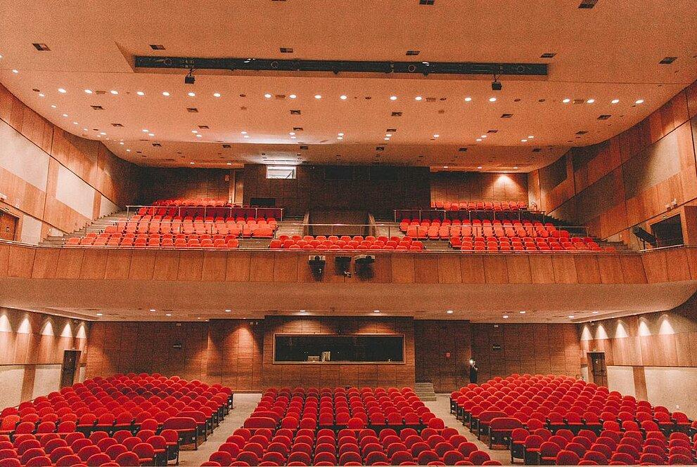 Auditório de dois andares com cadeiras vermelhas e vazias e bem iluminado