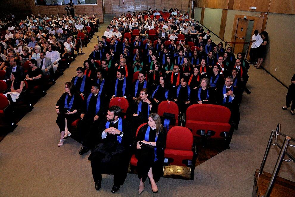 Alunos doutorandos sentados na plateia do auditório com togas de formatura.