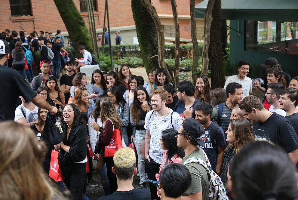 Novos alunos no campus recebendo brindes.