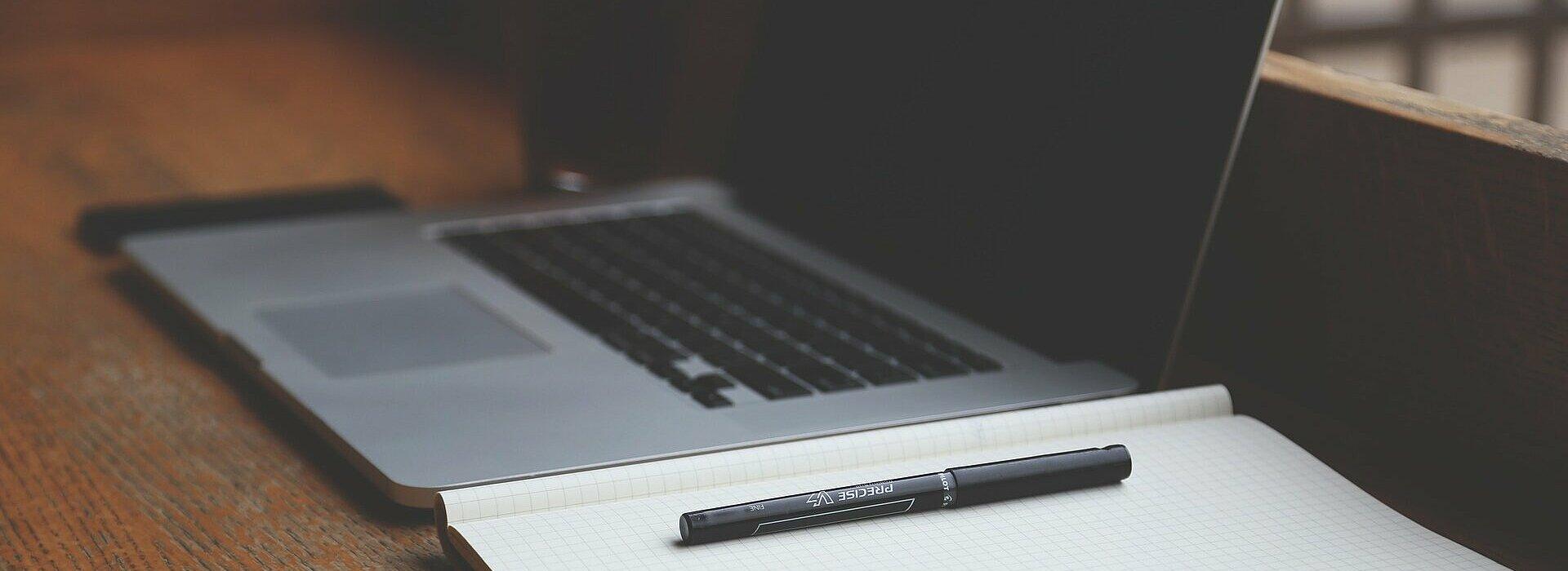 Notebook ao lado de caderno, ambos em cima da mesa.
