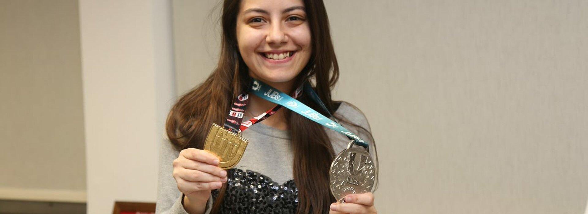 Júlia mostrando medalhas