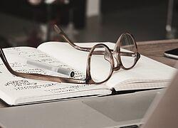 óculos e caderno em cima de uma mesa