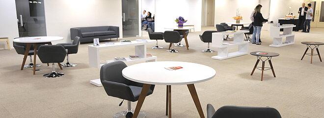 ampla sala com mesas e cadeiras para usos diversos