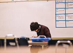 A foto, tirada de longe, mostra menino fazendo uma prova em uma sala de aula. Atrás podemos ver uma lousa.