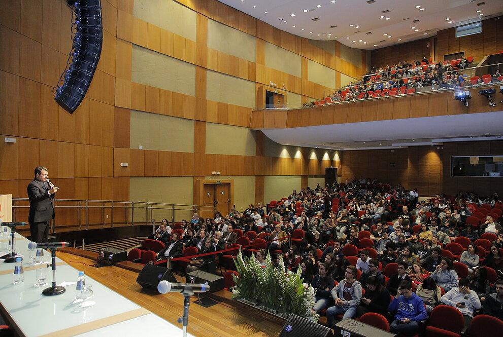 auditório cheio com muitas pessoas assentadas