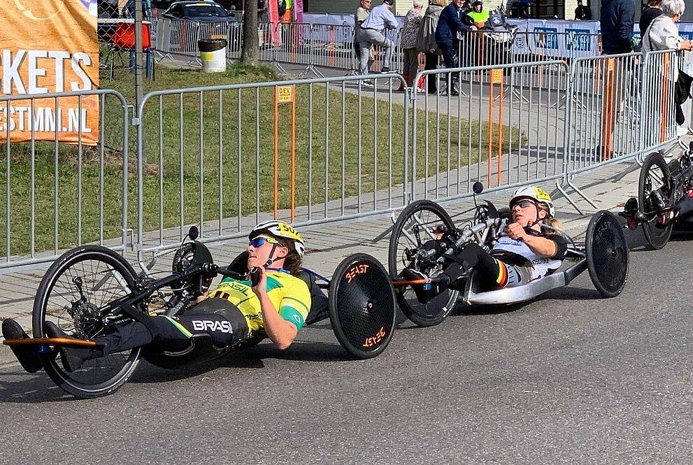 duas mulheres em uma competição de paraciclismo em bicicletas adaptadas