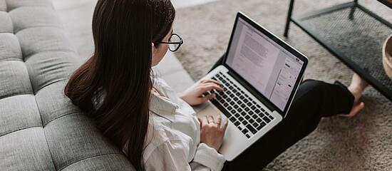 Estudante sentada no chão e mexendo em seu notebook