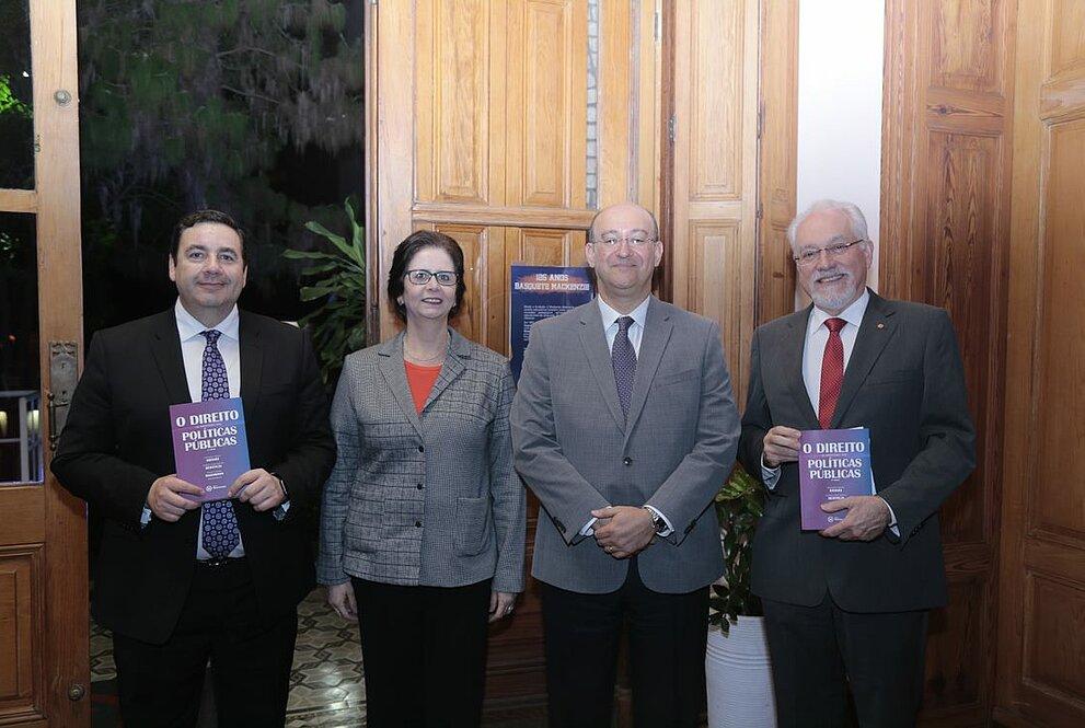 quatro pessoas em pé, mostrando livros