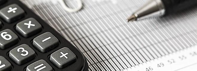 Imagem possui uma calculadora, uma folha e uma caneta