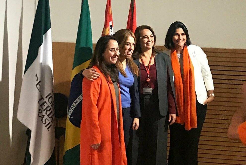 debatedoras posam para foto em frente às bandeiras do Brasil, Mackenzie e outras.
