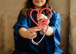 profissional da saúde segurando seu estetoscópio em formato de coração