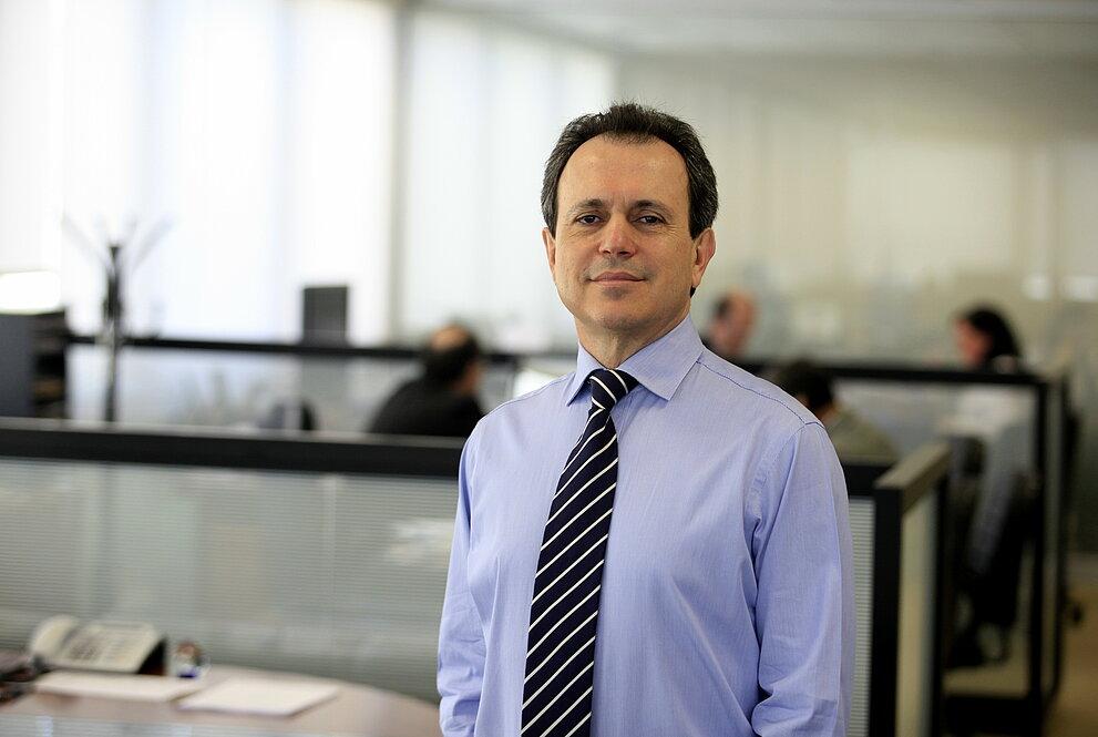 Maurício Meneses de camisa e gravata com escritório ao fundo.