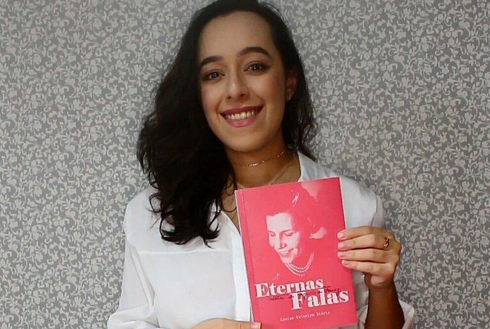 Autora Louise Teixeira Diório segurando seu livro