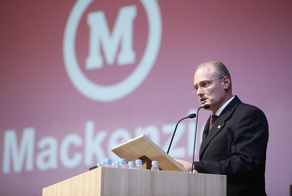 Coordenador do CCSA faz discurso ao púlpito com fundo vermelho com símbolo do Mackenzie