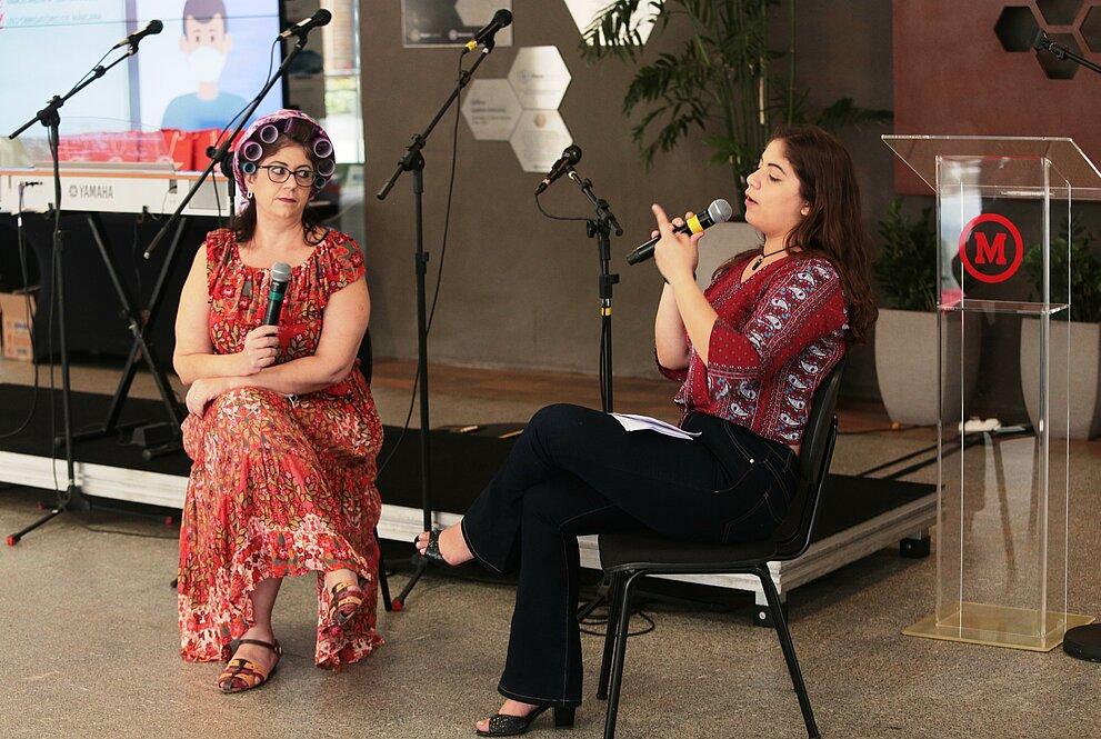 duas mulheres brancas sentadas, em roupas coloridas, conversam segurando microfones