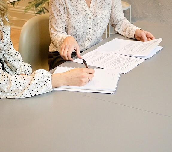 duas mulheres estão em uma mesa, uma delas está assinando um papel e a outra mexendo em outros papéis. as duas parecem estar resolvendo algum negócio. não conseguimos ver seus rostos.