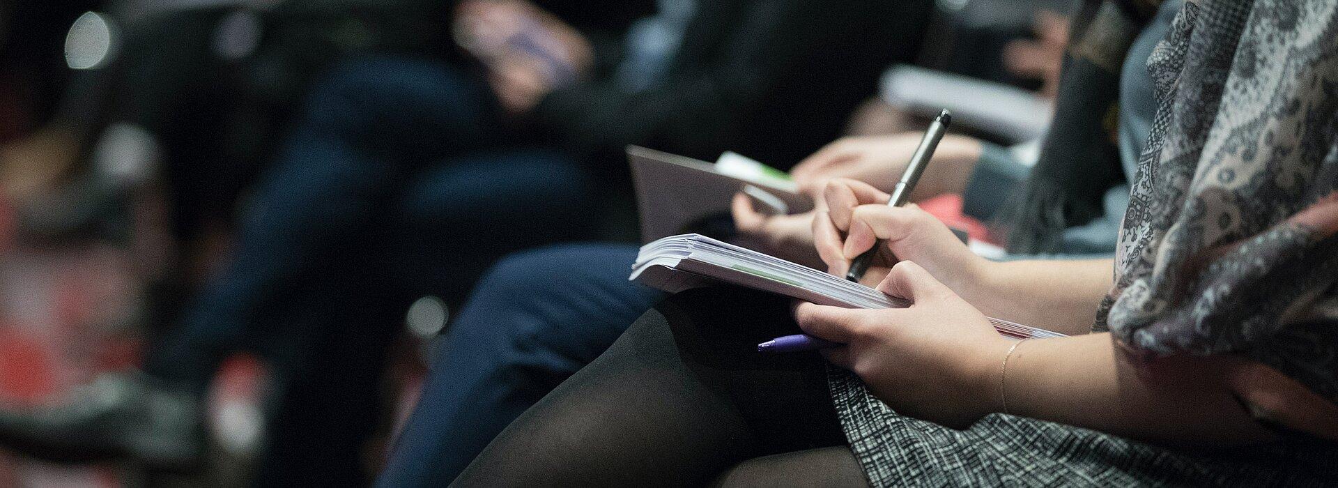 Na foto temos pessoas em uma palestra fazendo anotações