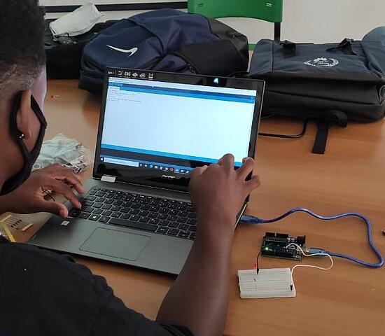 Na foto, um homem de costas usa um laptop, que está em cima de uma mesa, cheia de ferramentas, cabos e itens utilizados no curso de eletricidade.